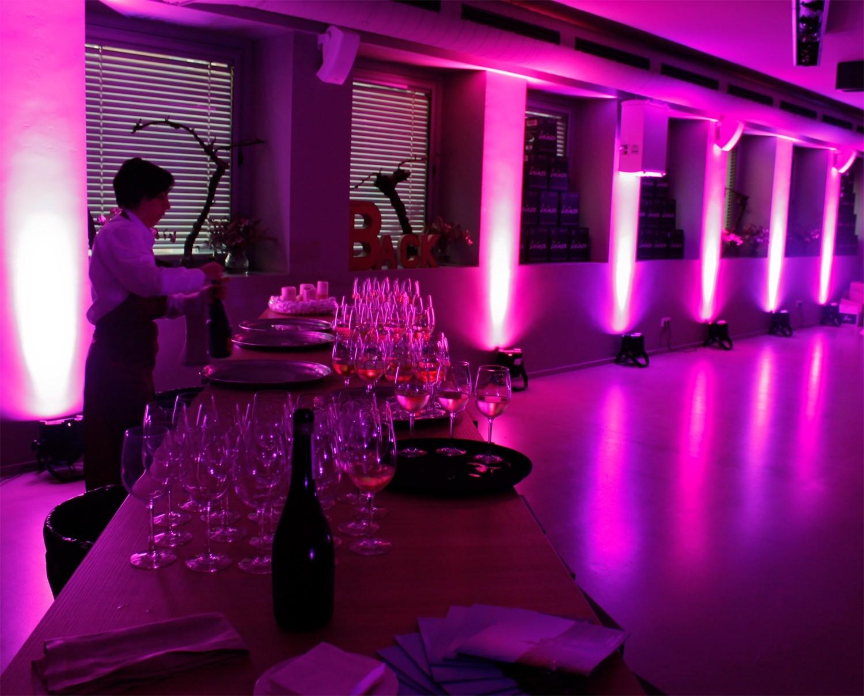 Mesa para servicio con copas y vino con el ambiente decorado en violeta en la sala BACK