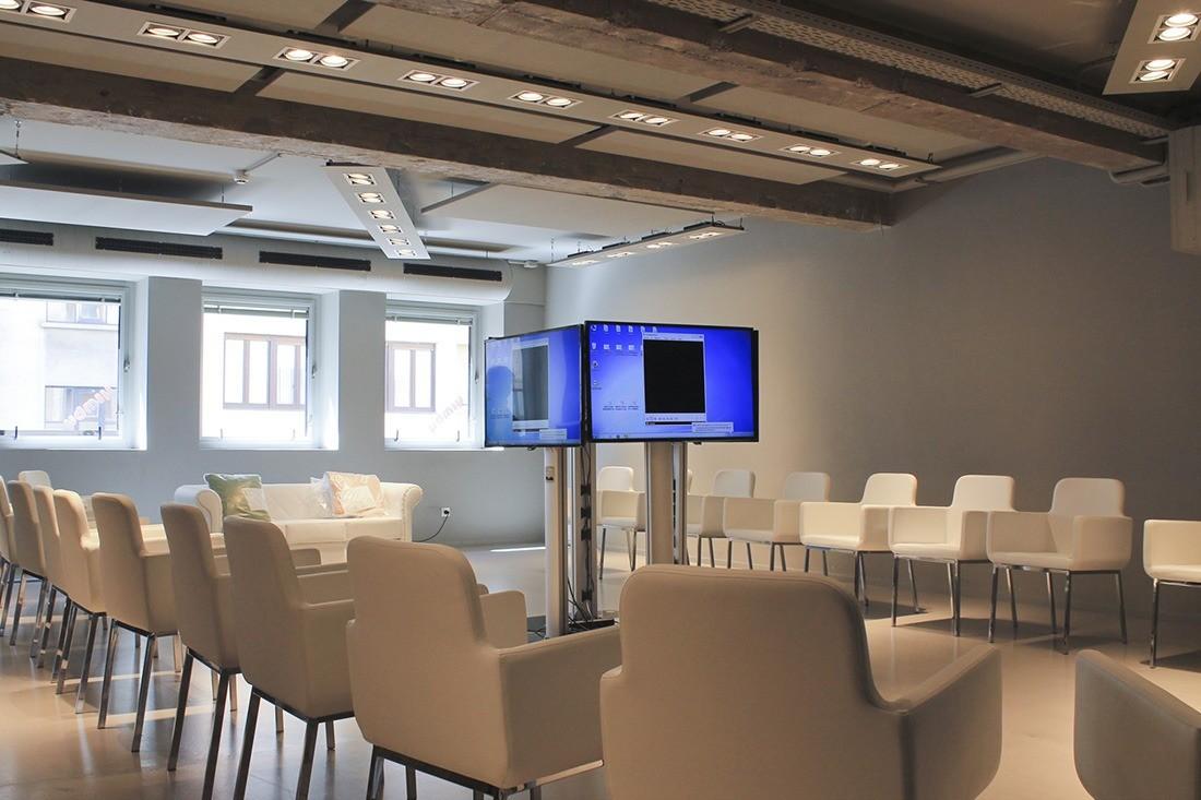 La sala MY con sillas blancas y televisores en el centro